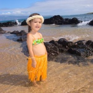 Little girl on the beach wearing a grass skirt.