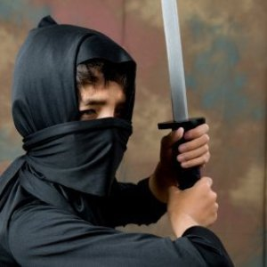 Young boy dressed in a ninja costume.