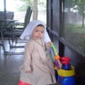 Infant in a tan and white nun costume.