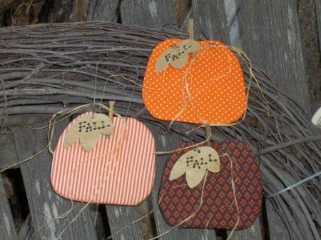 Three pumpkins against a branch wreath and weather wooden fence.