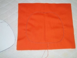 Outline of pumpkin sewn into square orange fabric.