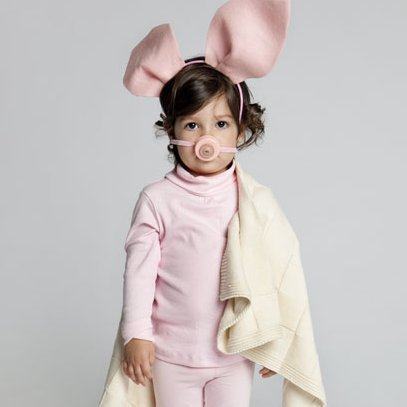 Little girl in a pink pig costume.