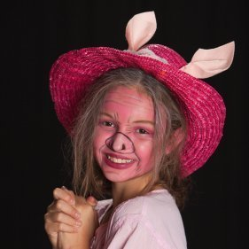 Girl wearing a pig costume with a pink straw hat.