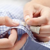 Sewing a button onto a blue checked shirt.