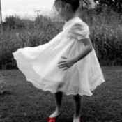 Little Girl Dancing in the Yard With Red Shoes