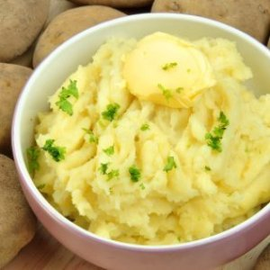 Bowl of mashed potatoes with potatoes in background.