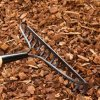 A rake laying on garden mulch.