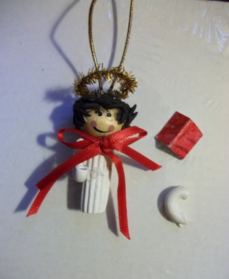 Angel with one arm removed to show placement. There are also construction instuctions regarding the arms, songbook, and atttaching rice hair.