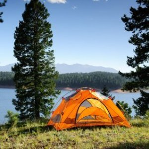 Orange camping tent pitched near a mountain lake.