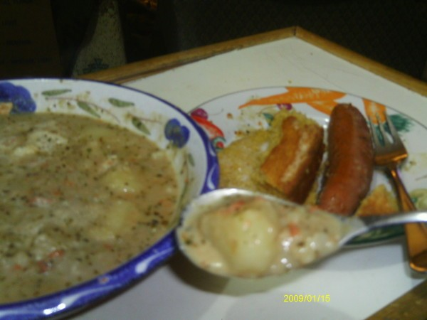 Bowl of the soup, some on spoon, and sausage on the side.