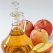 Apple cider vinegar in a glass decanter with apples.
