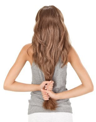 A woman with very long hair that she can reach behind and grab with both hands at her waist.