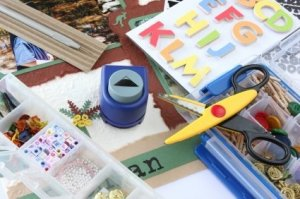 Craft supplies for scrapbooking, including scissors, punches, paper and other decorations.
