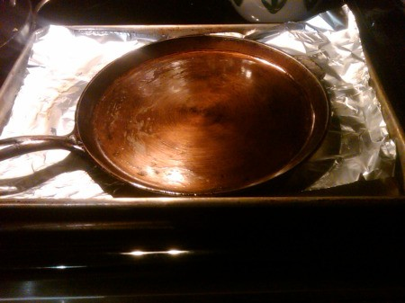 Cast iron griddle sitting on foil in baking pan.
