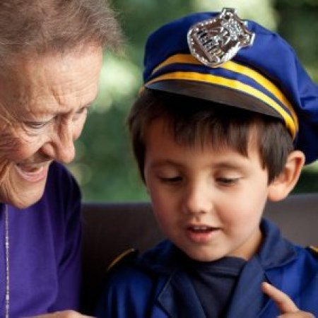 A young boy wearing a policeman costume, sitting with his grandmother.