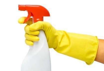 Gloved hand holding a spray bottle.