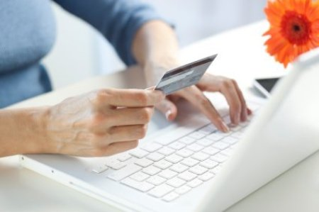 A woman typing in a credit card number for an online shopping purchase.