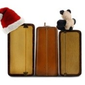 Photo of a suitcase packed for the holidays with a Santa hat on it.