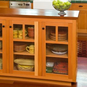 Bungalow style kitchen cabinet with glass paned doors.