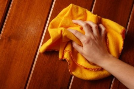 A hand holding a bright yellow cloth to polish a wood surface.