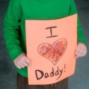 "Homemade Father's Day Gifts, A child holding a homemade card that says ""I love Daddy""."