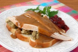 Photo of brown gravy on a turkey sandwich.