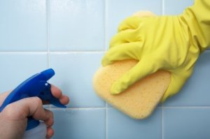 Picture of someone cleaning tile with a spray bottle and a sponge.