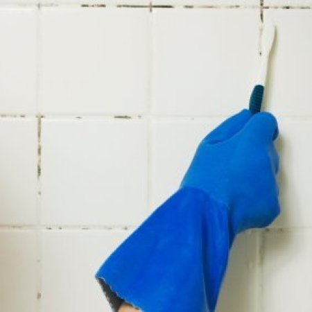Blue gloved hand cleaning mold on shower walls with a toothbrush.