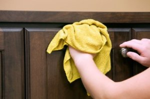 Homemade Kitchen Cabinet Degreaser Recipe, Rag in hand cleaning dark kitchen cabinet