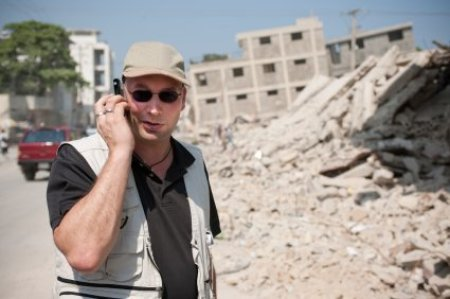Man talk on the Phone in Front of Collapsed Building