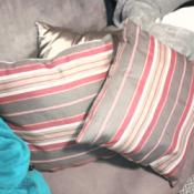 Gray, cream, and pink striped throw pillows.