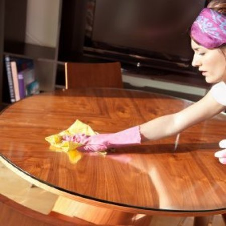 Woman dusting a table.
