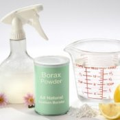 Borax powder, with a measuring cup and spray bottle.