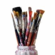 Paint laden art brushes in a jar.