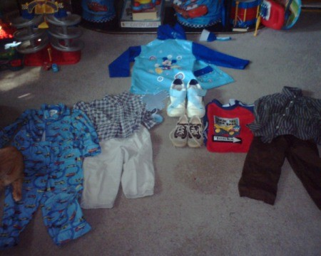 Flanel pajamas, rain coat, two pairs pants with matching shirts, another shirt, and a pair of shoes in toddler sizes as well as a pair of adult sneakers and a butterfly decoration.