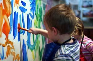 Photo of a kid finger painting.