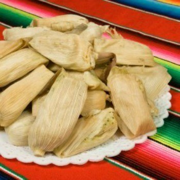 Tamales on white plate sitting on a zarape style tablecloth.