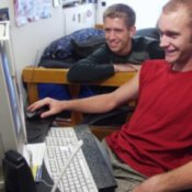Two guys looking at a computer in their dorm room.