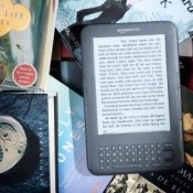Photo of a Kindle surrounded by books.