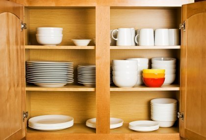 Organizing Your Kitchen, Dishes neatly organized in a wood cabinet.