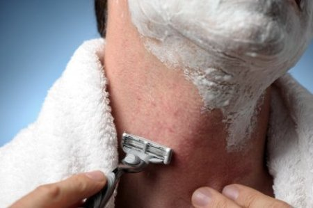 Man shaving neck with razor