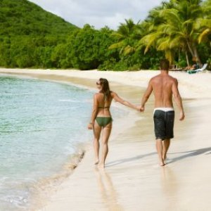 Saving Money on Your Honeymoon, A couple holding hands on a tropical beach.