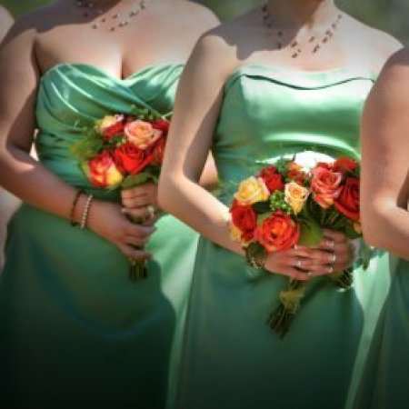 Bridesmaids in different green dresses.