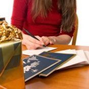 A woman filling out Christmas cards.