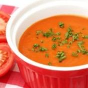Bowl of cream of tomato soup garnished with chives.