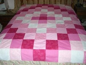 Pink and white simple patchwork quilt on bed.