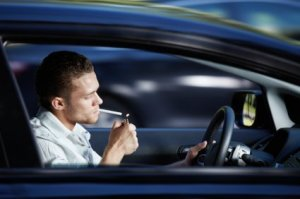 Man Lighting a Cigarette in his Car While Driving