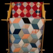 Two quilts hanging on a wooden rack.