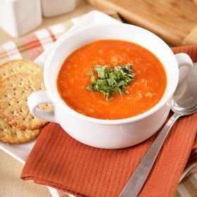 A bowl of tomato soup with crackers.