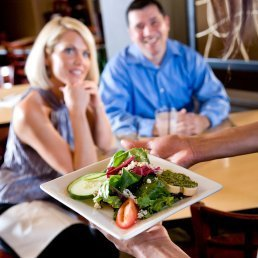 Couple being served a Salad